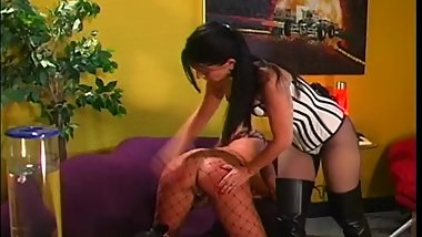 Lesbian domme in corset and thigh high boots spanking her sub