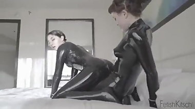 Lesbians in black latex fuck with strap on